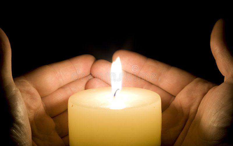 Hands trying to save the candle light stock image