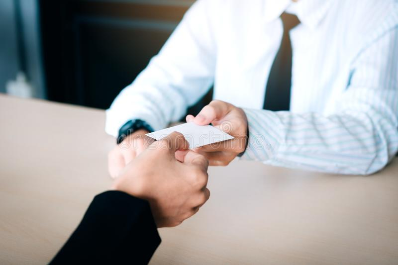 Hands of two business people sitting in office room giving and t stock images