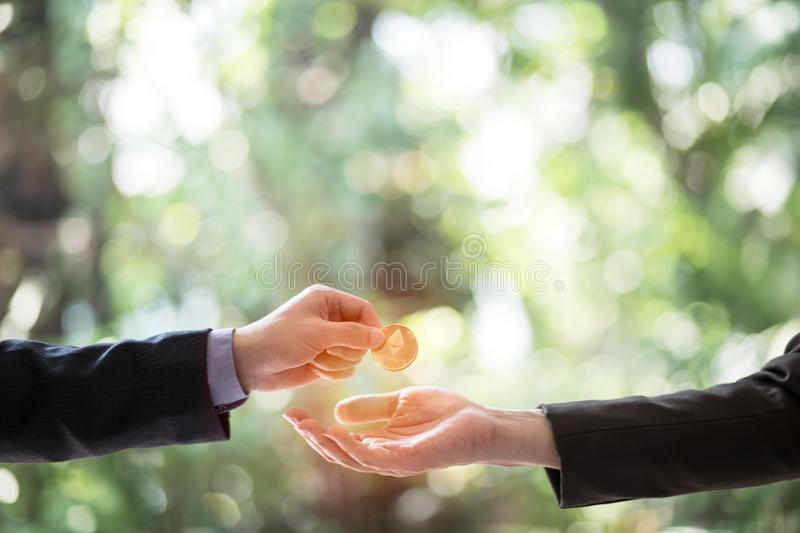 Hands of two businessmen are trading coin of ethereum. A symbolic coins of ethereum. electronic money exchange, royalty free stock photos