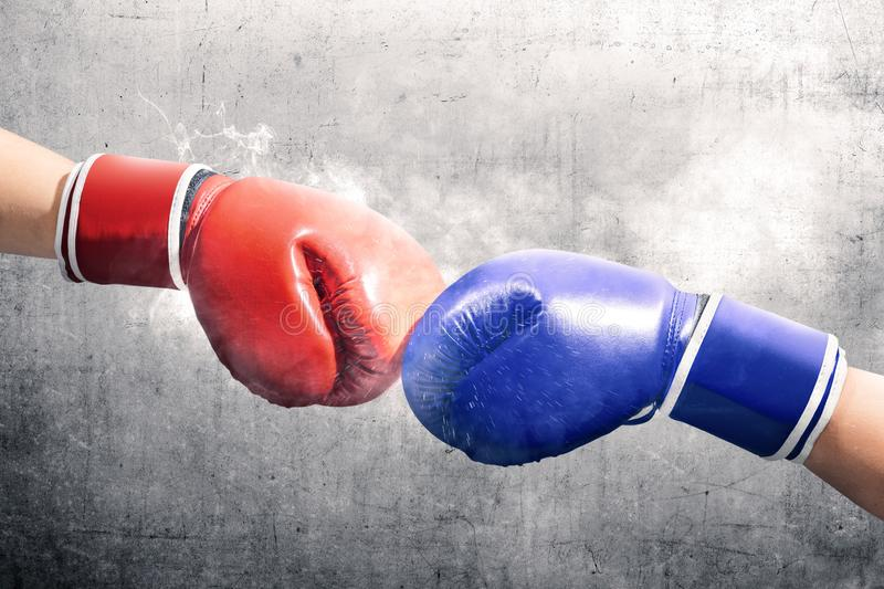 Hands of two men with blue and red boxing gloves bumped their fists. Over black wall background royalty free stock photos