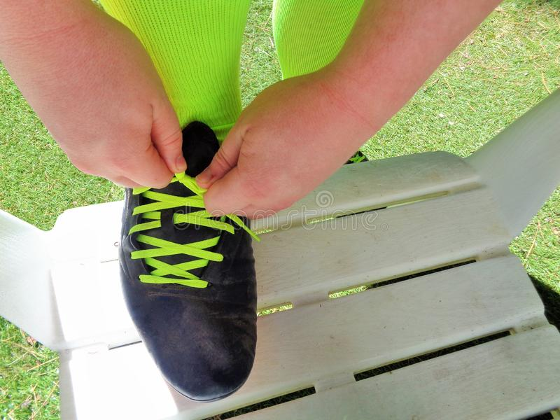 Hands Tying Shoelaces on Soccer Football Cleats. This is an image of man tying the laces on his soccer cleats. It is a bright sunny morning outside. He is stock images