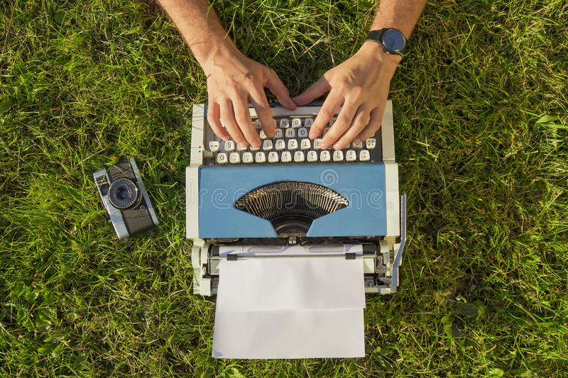Hands on typewriter outdoor. Human hand prints on retro typewriter in the grass stock photos