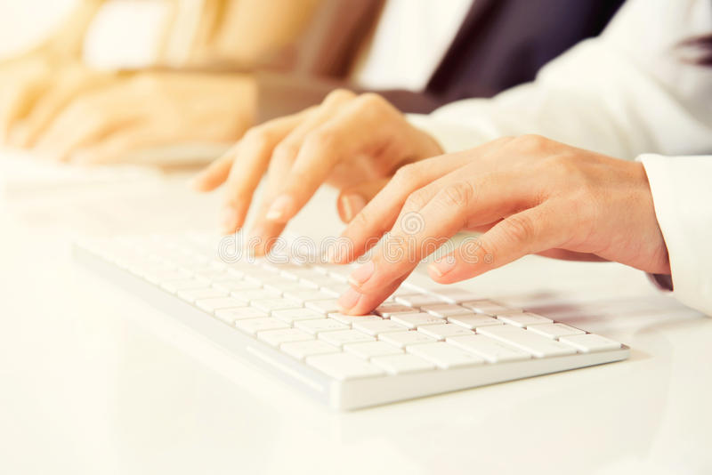 Hands typing on computer keyboards. Hands typing on white computer keyboards royalty free stock image