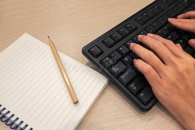 Hands typing keyboard with a blank notepad and pencil on wooden stock image