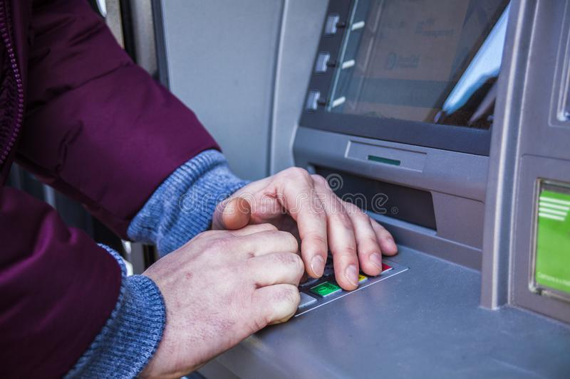 Hands typing PIN at ATM machine for cash money withdrawal. Close up for hands typing on ATM maschine royalty free stock image