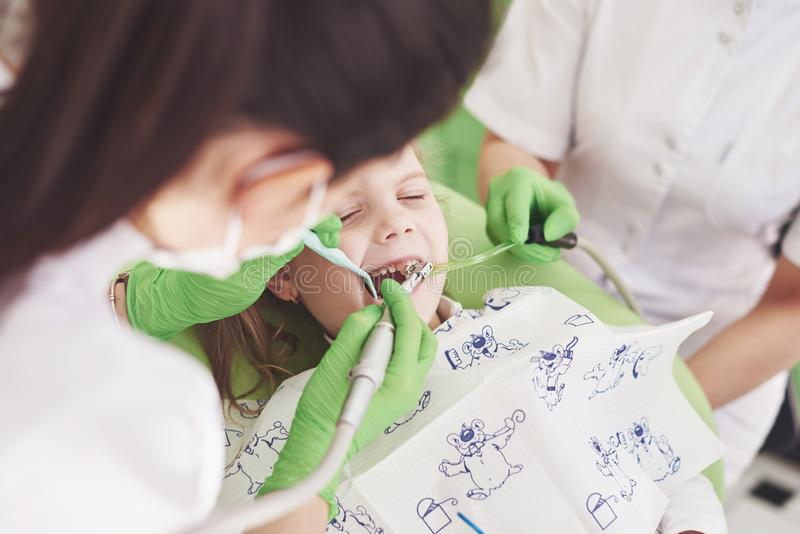 Hands of unrecognizable pediatric dentist and assistant making examination procedure for smiling cute little girl royalty free stock photo
