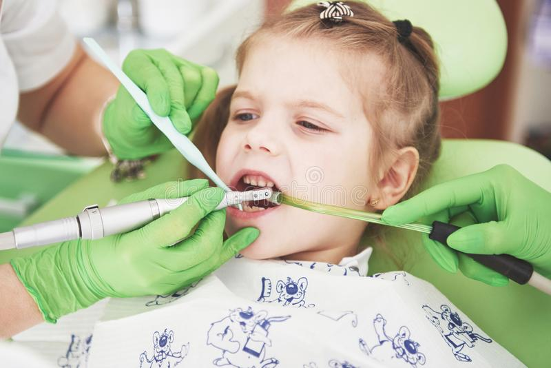 Hands of unrecognizable pediatric dentist and assistant making examination procedure for smiling cute little girl stock photography
