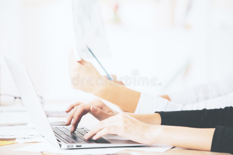 Hands using laptop closeup. Close up of lady`s hands using laptop computer placed on messy office desktop royalty free stock photo