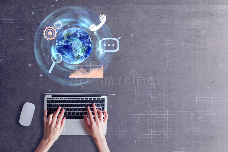 Hands using laptop with globe stock photo
