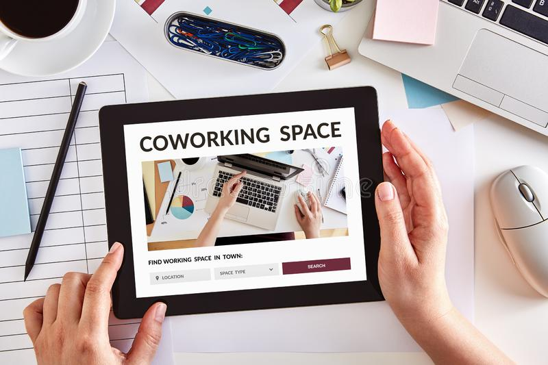 Hands using tablet with coworking space concept on screen stock photos