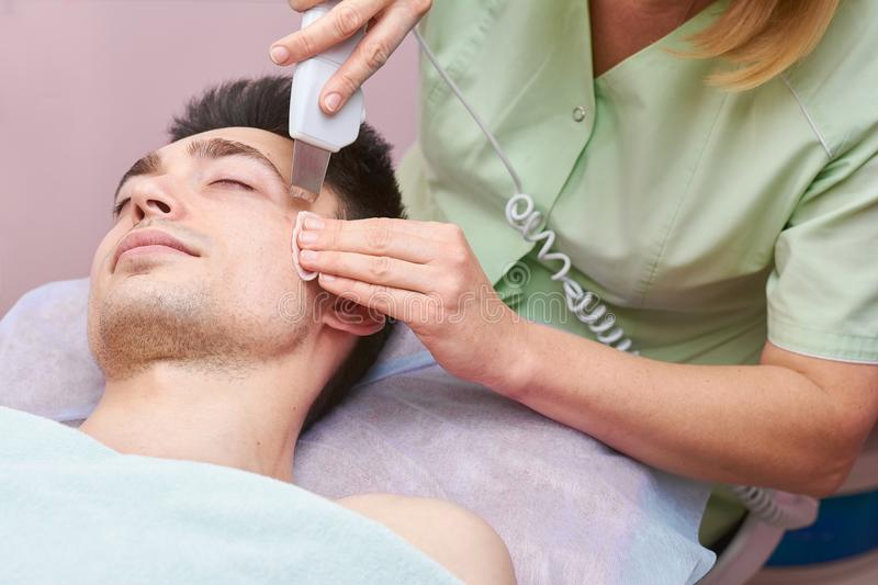 Hands using ultrasonic face scrubber. royalty free stock image