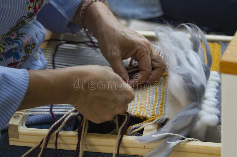 Hands on Vertical tapestry with beige yellow and blue  thread royalty free stock photo