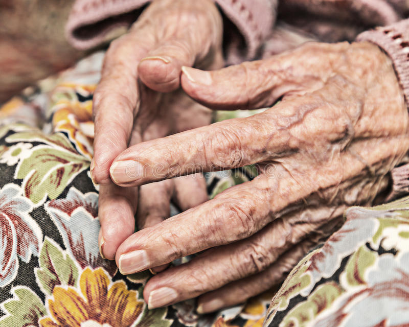 Hands of a very old woman kneeling. royalty free stock image