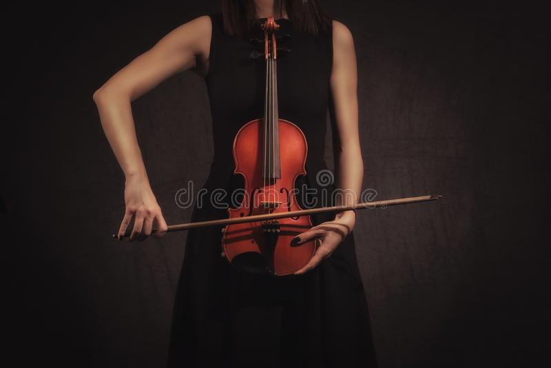 Hands of Violinist Woman. Playing violiln on black background royalty free stock photos