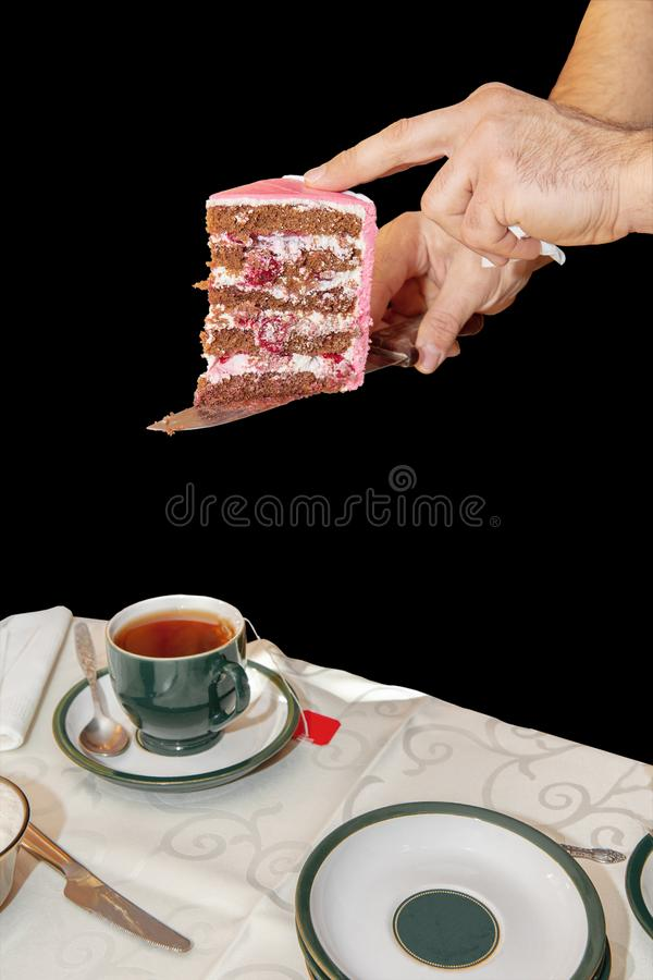Hands waiter serves a piece of fruit cake in pink glaze on a family celebration-wedding, birthday. Isolated on black background royalty free stock image