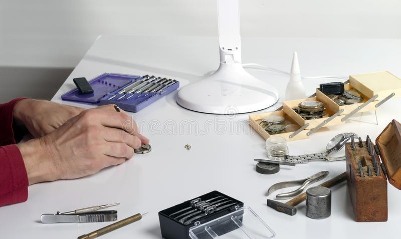 The hands of a watchmaker repairing a mechanical watch. Workplace of the clockmaker for the repair of mechanical watches stock photos
