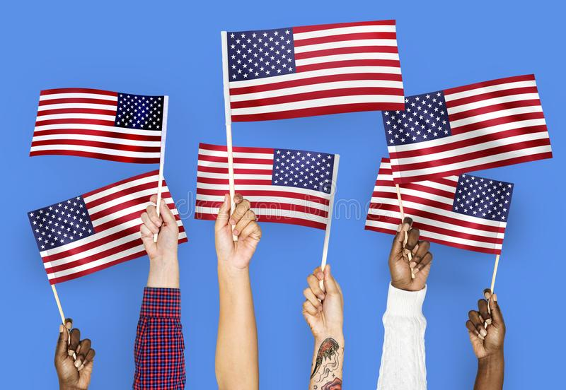 Hands waving flags of the United States stock images