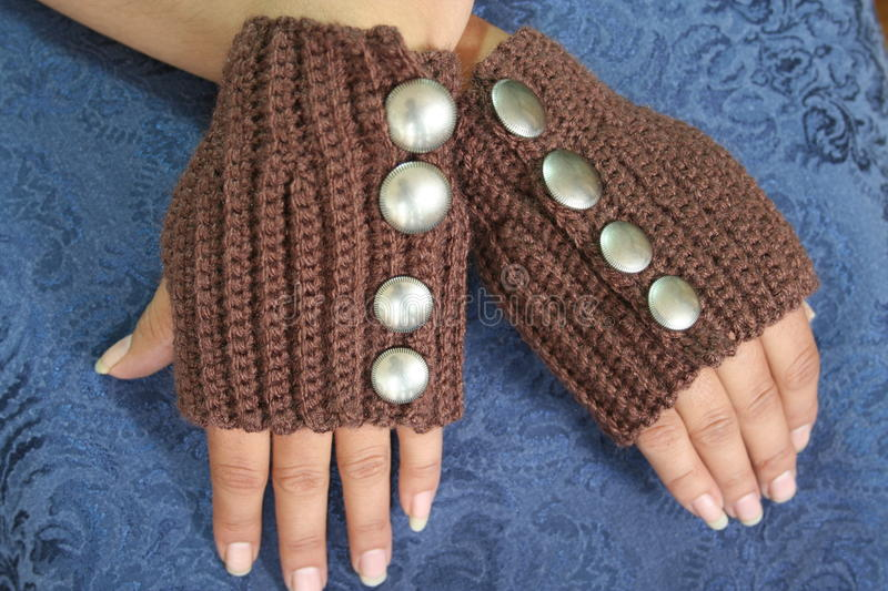 Hands Wearing Fingerless Gloves. Hands of an Alaska Native woman wearing brown rib stitch crochet fingerless gloves with large metallic buttons royalty free stock photos