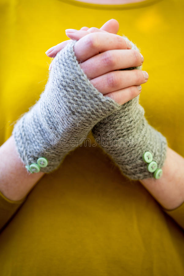Hands Wearing Knitted Fingerless Gloves. Hands wearing knitted woolen fingerless gloves stock photos