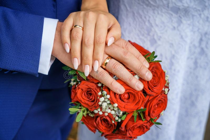 Hands with wedding rings on the bride`s bouquet stock image