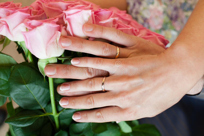 Hands with wedding rings and fower bouquet stock photography