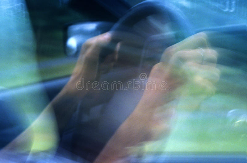 Hands On The Wheel. A drivers hands anxiously grip the steering wheel in this intentionally blurred, time-lapse image stock image