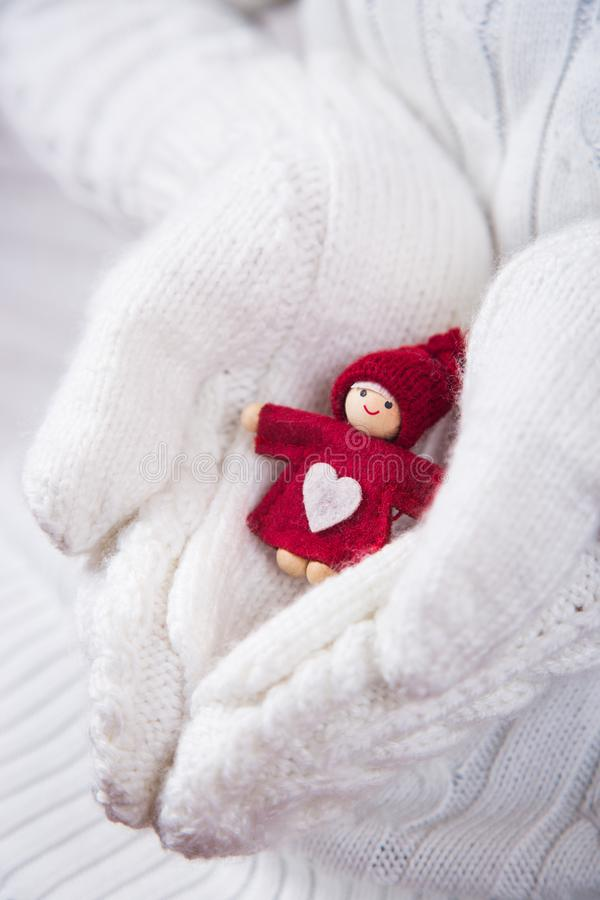 Hands in white knitted mittens holding little red Christmas doll with heart. stock photos
