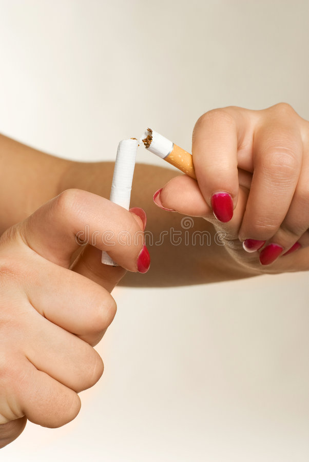Hands of a woman breaking a cigarette royalty free stock photography