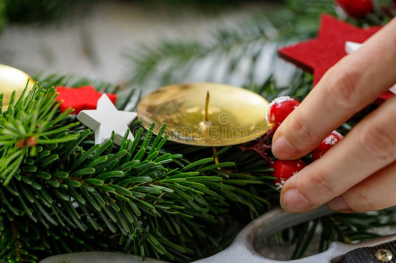 Hands of a woman decorate Christmas Advent wreath from fir twigs stock images