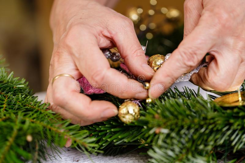 Hands of a woman decorate Christmas Advent wreath from fir twigs stock photos