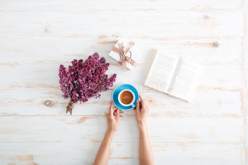 Hands of woman drinking coffee and reading book on table stock photo