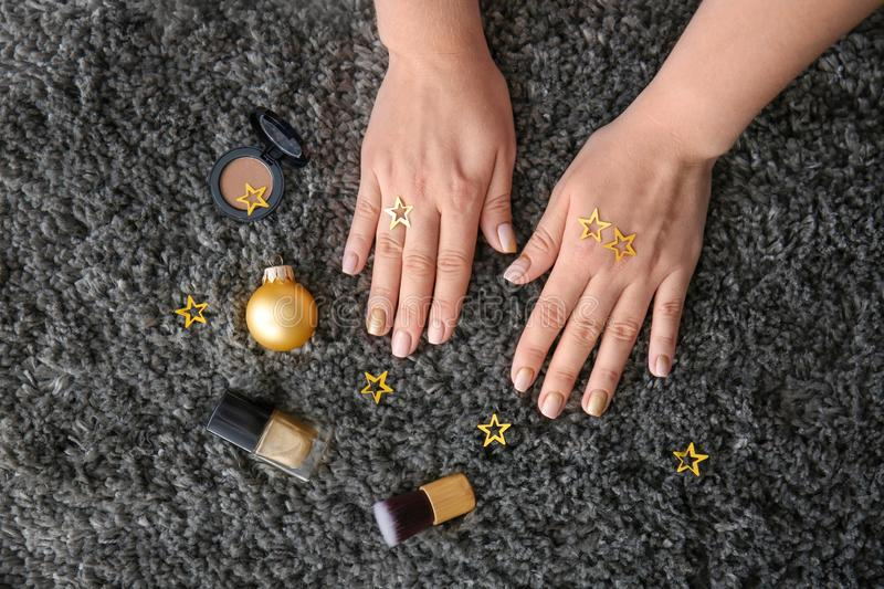 Hands of woman with festive manicure, Christmas decor and nail polishes on carpet royalty free stock photography