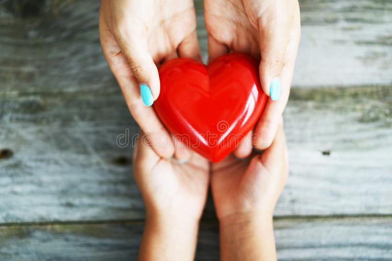 Hands of woman giving a shiny red heart to her daughter, sharing love concept royalty free stock images