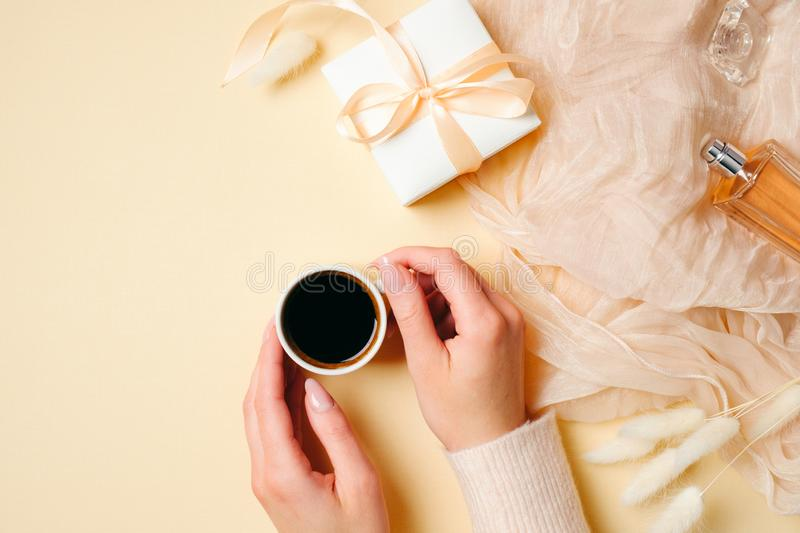 Hands of woman holding coffee cup on beige feminine background with stylish accessories, perfume bottle, silk scarf, gift box. Top stock photos