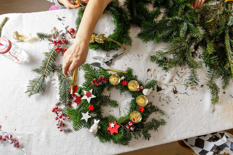 Hands of a woman make Christmas Advent wreath from fir twigs royalty free stock images