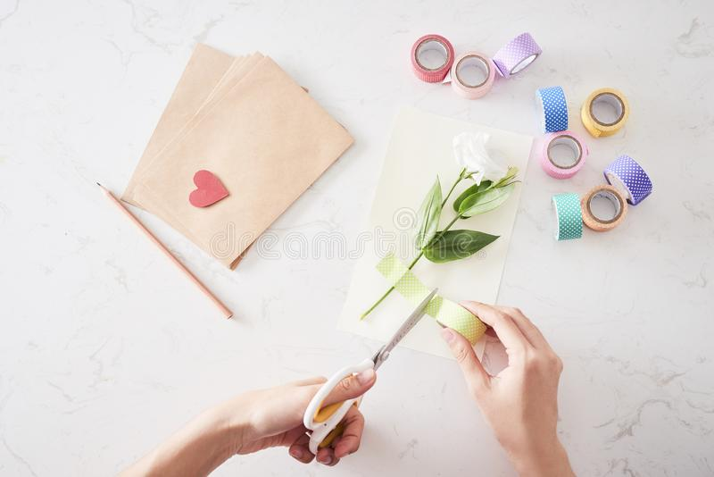Making decorations or greeting card. Paper strips, flower, scissors. Handmade crafts on holiday stock image