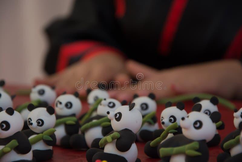 Hands of woman making plasticine panda bears on red background. Macro stock photo