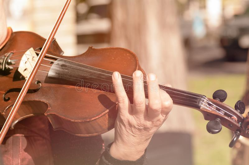Hands of a woman playing the violin. Close-up stock photography