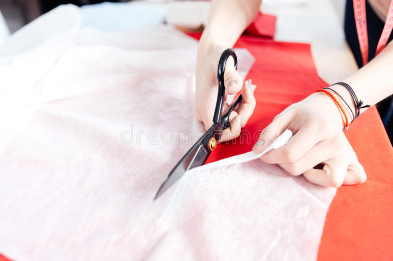 Hands of woman seamstress with scissors cutting fabric. Hands of young woman seamstress with scissors cutting white fabric stock photo