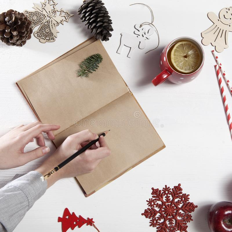 Hands of a woman who is going to draw by pencil in notebook. On table there is a cup of tea with lemon, snowflake, christmas toys stock images