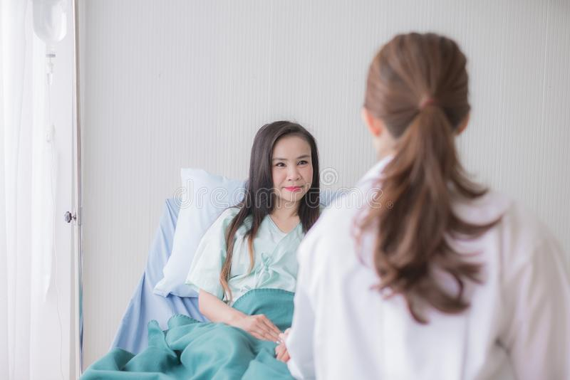 Hands women doctor reassuring her female asian patient in hospital room,Dentist giving a consultation and encouragement to patient. Hand women doctor reassuring stock photo