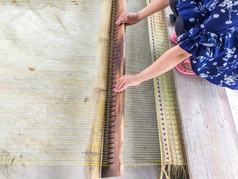The hands of women woven mats traditional are products handmade in countryside of Thailand.  stock photos
