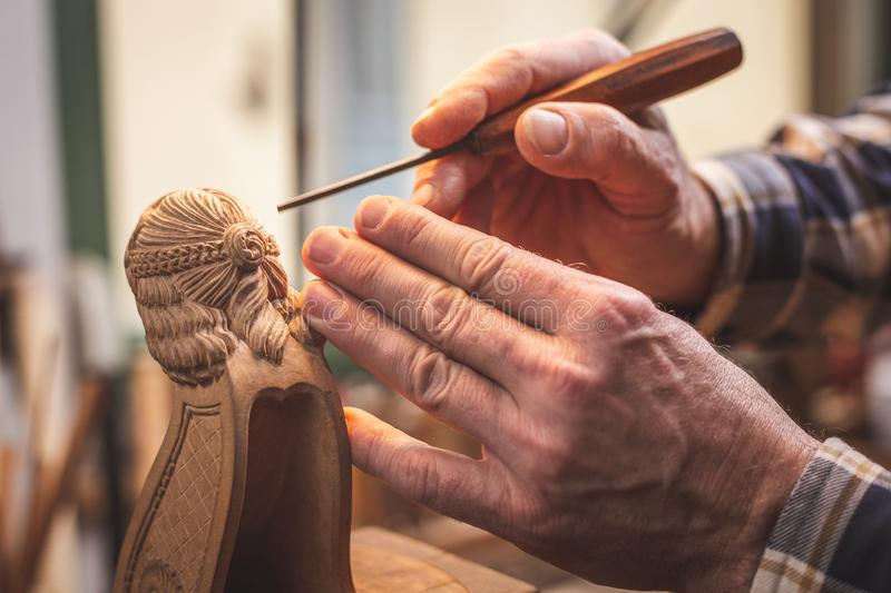 Hands of a wood sculptor working on a small wooden figure. Close up of two hands of a mature man holding a carving tool next to a wooden figure that is being royalty free stock images