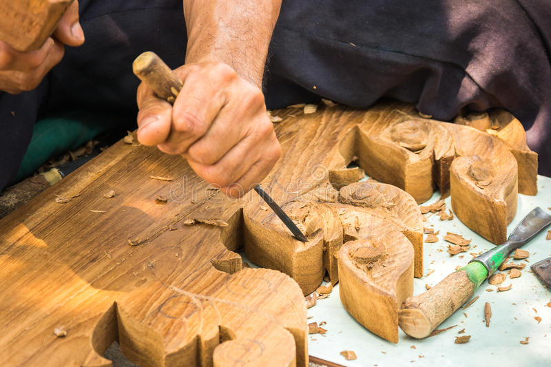 Hands woodcarver while working with the tools. Carpenter tool hammer in hand working wooden royalty free stock image