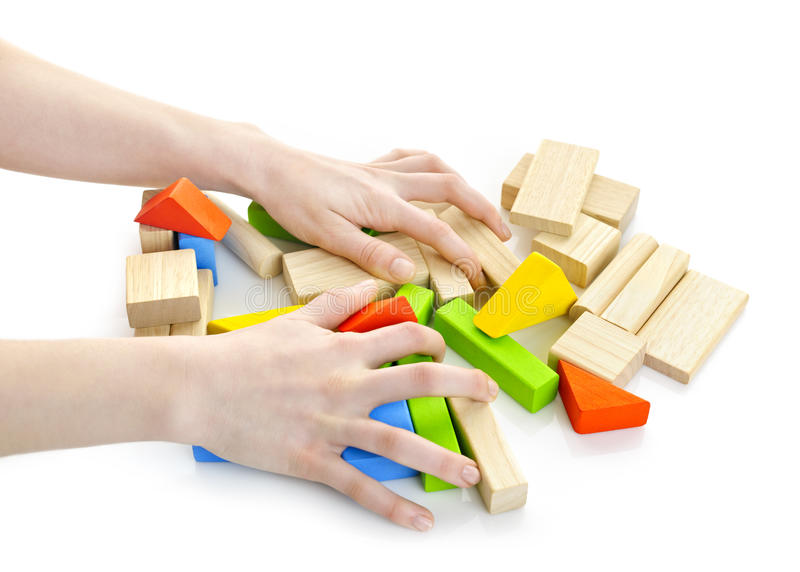 Hands with wooden block toys. Hands with pile of wooden block toys isolated on white stock photo