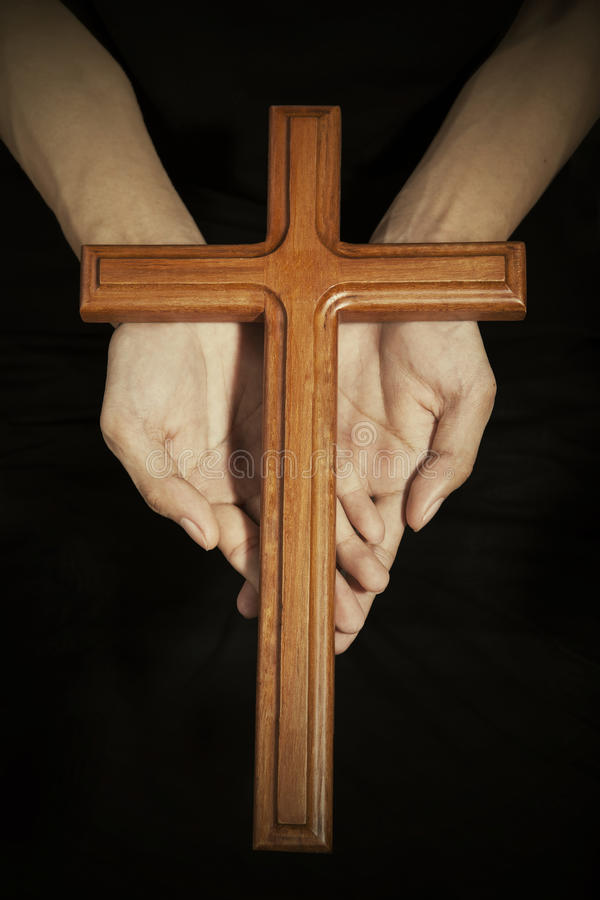 Hands with wooden cross on the palms. Closeup of wooden cross on the prayer palms, symbolizing christian person is praying stock image