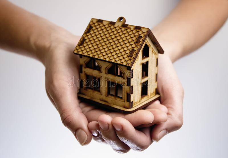 Hands with wooden house model. Concept of rent, purshase, insuranse, building real estate, eco house and other stock images