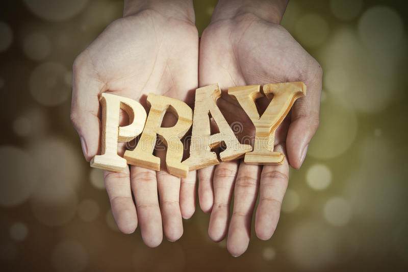 Hands with a word of pray in bokeh background royalty free stock images