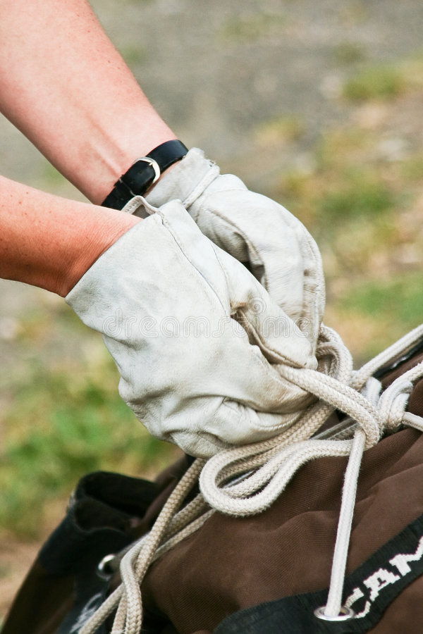 Hands at work. Two hands with gloves bundling up a bag royalty free stock photos