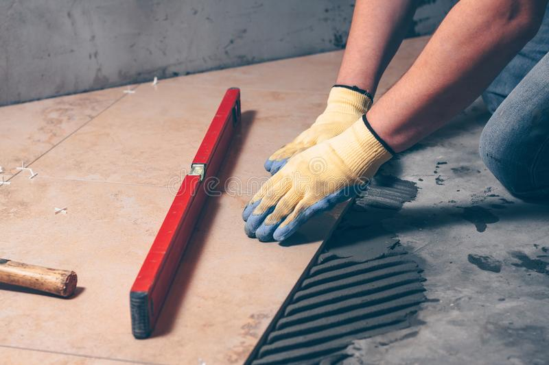 The hands of the worker in gloves press the tile to the floor stock image